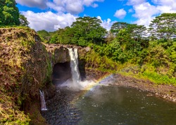 Waterfall with rainbow in Hawaii, also know as Waianuenue Falls that flows 80 feet over a natural lava cave into a turquoise pool of water surrounded by dense forest.