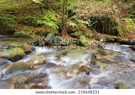 Waterfall with trees and rocks in mountain in Autumn