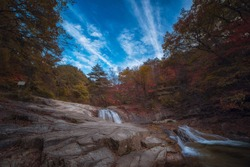 Waterfall with trees red leaves, rocks and stones in autumn forest at Bangtaesan Mountain,Inje Gangwondo,South Korea.