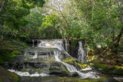 Waterfalls cascading down large rocks surrounded by lush natural green forest trees & fauna in the Presidente Figueiredo region of the Amazon rainforest in the state of Amazonas, Brazil, South America