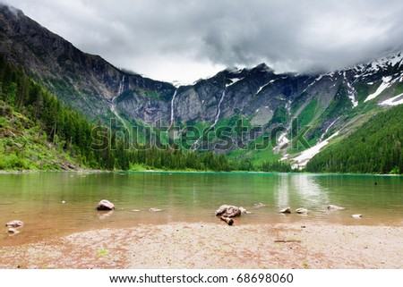 Waterfalls cascasde down steep mountain sides into Avalanche Lake, Glacier National Park. - stock photo