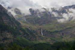 Waterfalls surrounded by mountains and a glacier circus in Bielsa, Huesca, Aragon, Spain. Alpine and foggy landscape in Ordesa and Monte Perdido National Park, Spanish pyrenees.