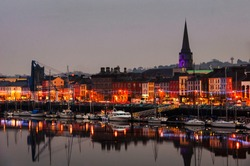 Waterford, Ireland. Panoramic view of a cityscape at night with illumination in Waterford, Ireland. It is the oldest city in the country where located many restaurants, shops, bars. Moored boats