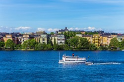 Waterfront color buildings with black roofs. View of Kungsholmen from Langholmen. White old ferryboat with red and black pipe. Walking riverboat on Lake Malaren. Bright sunny day. Competition in speed