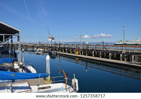 Waterfront of Edmonds in Washington state, view towards the pier and marina, a ferry on the right sight on horizon #1257358717