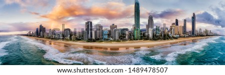 Waterfront of Surfers Paradise Gold Coast city scape urban towers over wide sandy long beach on Australian Pacific coast in Queensland - aerial panoramic view from sea.