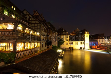 Waterfront restaurant and Ill river at night, Strasbourg, Alsace, France