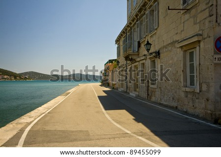 Waterfront road in Tisno with houses