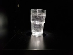 waterglass with bubbles in dark room illuminated