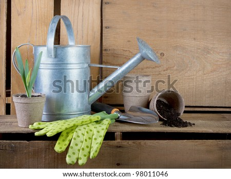 Watering can and gardening tools on wooden crates with wooden crates for background.
