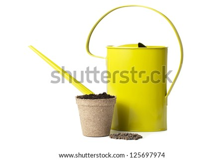Watering can and pot of soil beside a pile of brown seeds