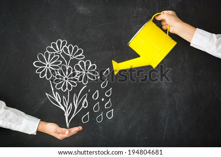 Watering-can in hand against blackboard
