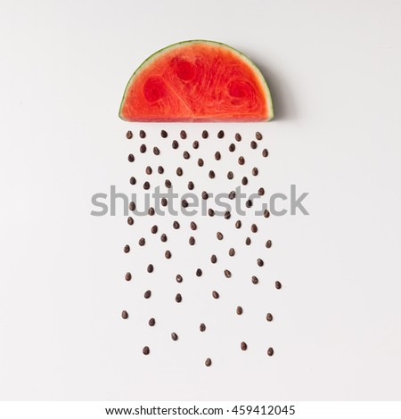 Watermellon slice with seeds raining. Flat lay. Weather concept.