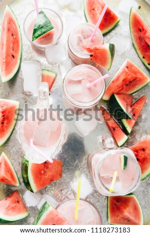 Watermelon an strawberry agua fresca cocktail , summer fresh drink on different glass container over a silver plate background and with pics of watermelon and melted ice around