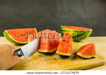 Watermelon cut with a knife on portions on a chopping board.