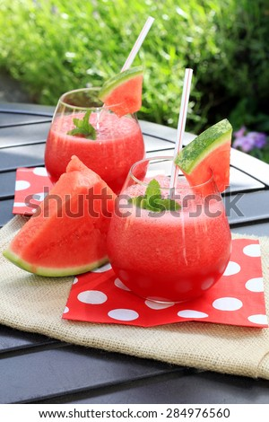Watermelon drinks outside in the garden with straws and fresh mint.
