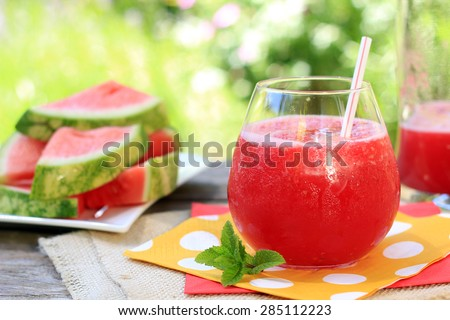 Watermelon drinks outside in the garden with straws and fresh mint. Also available in vertical.