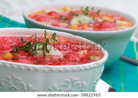 Watermelon Gazpacho made with watermelon, yellow peppers, cucumber, and garnished with a sprig of fresh thyme.