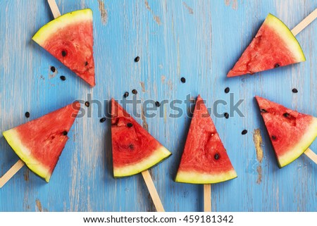 Watermelon popsicles and seeds over grunge blue wooden background. Space for text. Top view - Shutterstock ID 459181342