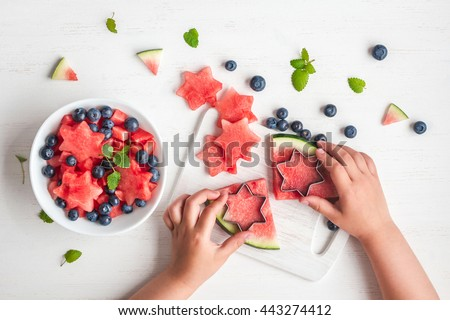 Watermelon salad. Slices of watermelon in the shape of a star. Children's hands cooking fruit salad on white table. Top view, flat lay