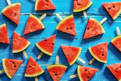 Watermelon slice popsicles on a blue rustic wood background
