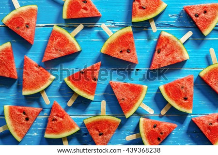 Watermelon slice popsicles on a blue rustic wood background, Popular summer fruit with yummy watermelon, Flat lay photography of Watermelon slice popsicles