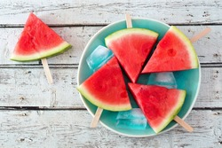 Watermelon slice popsicles on a vintage blue plate and rustic wood background