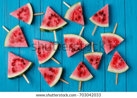 Watermelon slice popslices on a blue wooden background. Freshness, fruits, fruity texture for design - Shutterstock ID 703042033