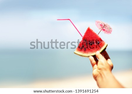 Watermelon slice, woman hands holding it against blue sky. Summertime concept #1391691254