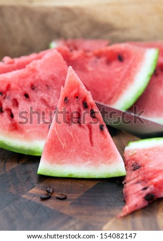 Watermelon slices on cutting board with knife on the wooden background