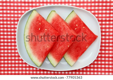 Watermelon Slices on dish on red and white checkered background