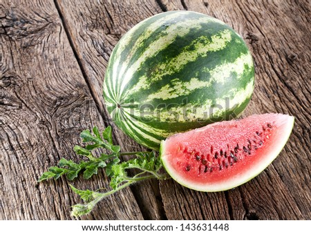 Watermelon with a slice and leaves on a wooden table.