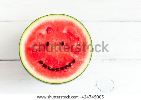 Watermelon with smile face. Funny watermelon on wooden white background. Top view, flat lay, copy space