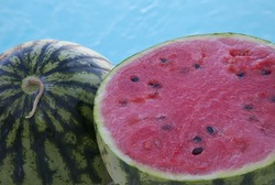 Watermelons.  Whole and slice of Summer fruit with blue water background.