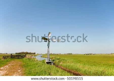 watermill in vertical Dutch landscape with meadows and ditch
