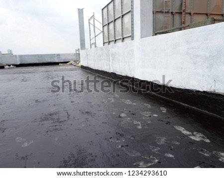 Waterproof coatings applied on flat roof concrete surfaces. There are several layers and layers of fiber mesh added to strengthen the bonding of the waterproofing layer.  #1234293610