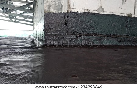 Waterproof coatings applied on flat roof concrete surfaces. There are several layers and layers of fiber mesh added to strengthen the bonding of the waterproofing layer.  #1234293646