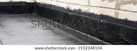 Waterproofing flat roof terrace with roll bitumen. Roof waterproofing. Bitumen insulating layer. Covering roofing material. Flat roof installation. Roofing felt