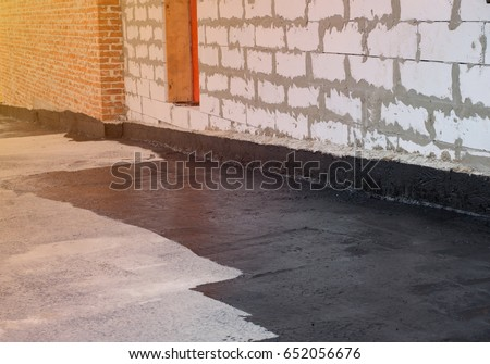 Shutterstock Waterproofing. Worker covered surface, bitumen primer for improving adhesion during surfacing,  rolled waterproofing, during the installation of isolation on industrial or household objects