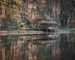 Waterreflection of a cabin at a lake in the middle of the forest, while the sun is going down.