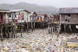 Waters filled with plastics in floating wooden village on the coast of Port Moresby, the capital of Papua New Guinea. Environmental problem, catastrophe