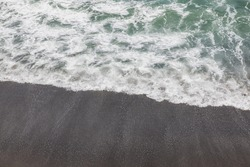 Waterscape background. Black sand beach with white milky foam waves. Nature and environment concept. Black and white contrast. Copy space. Volcanic beach in Bali, Indonesia
