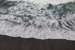 Waterscape background. Black sand beach with white milky foam waves. Nature and environment concept. Black and white contrast. Daylight. Copy space. Volcanic beach in Bali, Indonesia