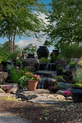 Waterscape fountain urns create a beautiful tranquil backyard oasis surrounded by bright pink and red flowers and ornamental grasses