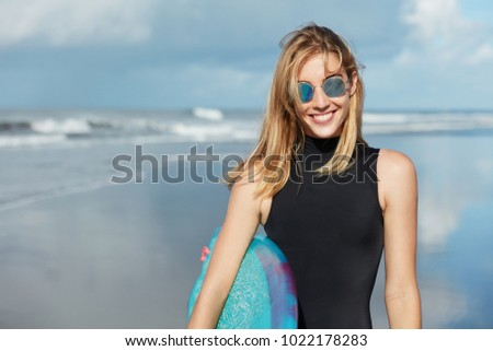 Watersport summer activities and recreation concept. Smiling beautiful young woman in shades and swimsuit, holds surfboard, poses against ocean background, being in good mood as likes her hobby