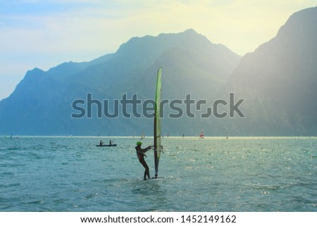 Watersports at a lake surrounded by mountains (Lake Garda, Torbole, Italy) #1452149162