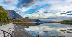 Waterton Lakes National Park lakeshore in autumn foliage season morning. Blue sky, colourful clouds reflect on lake surface like a mirror in sunrise. Fall color landscape. Landmarks in Alberta, Canada