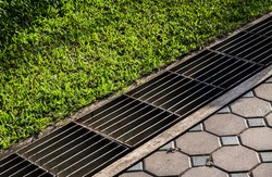 waterway and road - grass. Aqueduct between nature and city. iron grate of water drain in grass garden field. Steel rusty grating in the Grass garden and concrete. Manhole cover metal and way - grass.