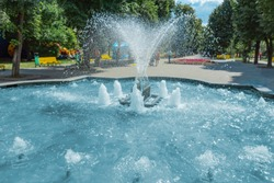 Waterworks fountain with water sprays and geysers in park or garden. Summer day time freshness and relax concept. Blue aqua pool and green trees