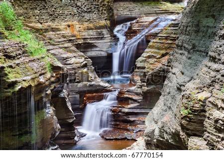 Watkins Glen waterfall in woods with rocks and stream in Watkins Glen state park in New York State